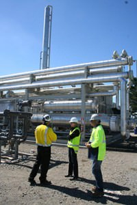 Gas-to-gas exchanger with the de-ethanizer tower in the background, on a beautiful New Zealand fall day.