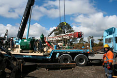 The cranes haul the derrick up.